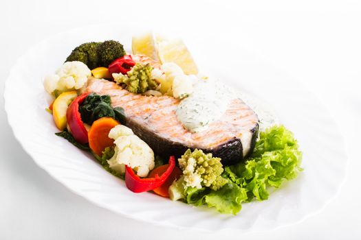 A grilled salmon steak with vegatable and lemon sauce