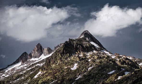 Beautiful mountainous landscape, Alpine mountains, dark cloudy sky, majestic nature, travel and tourism concept
