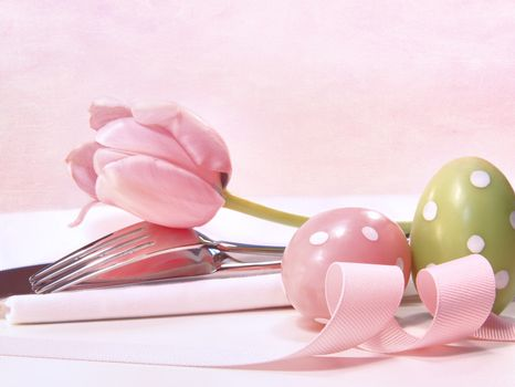 Closeup of utensils and pink tulip on pink