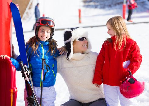 snow winter family in ski track mother and daughters smiling happy with equipment