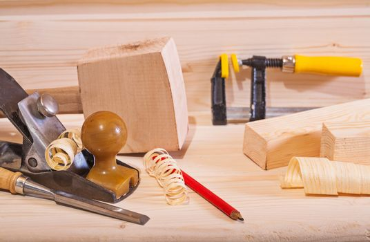woodworking plane with other tools on wooden board