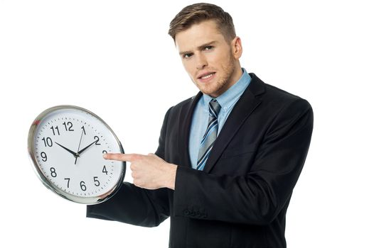Young business man holding wall clock