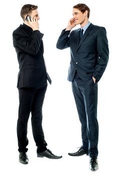 Two businessmen talking on cellphone