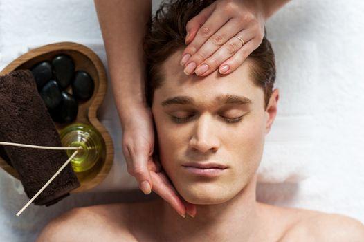Masseuse doing facial massage