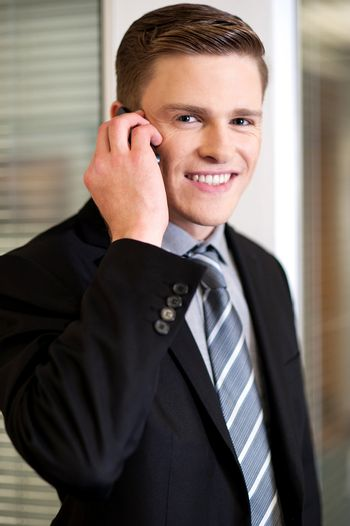 Smiling corporate guy attending phone call