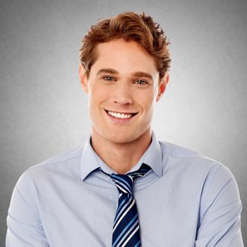 Young smiling executive posing over grey background