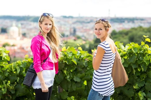 Two pretty, young women sightseeing in Prague historic center