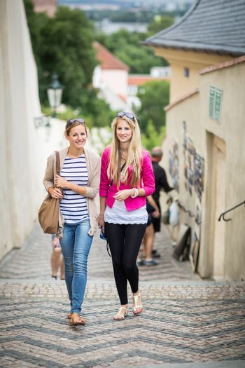 Two pretty, young women walking in the Prague historic center