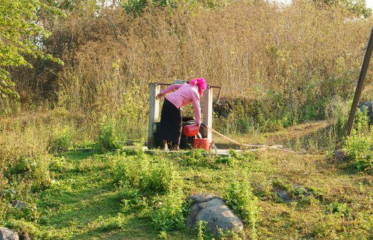 DAKLAK, VIETNAM- FEB 6: People  scoop water from water well by bucker, woman wear colorful clothing, the well at meadow in Vietnamese countryside, Viet Nam, Feb 6, 2014