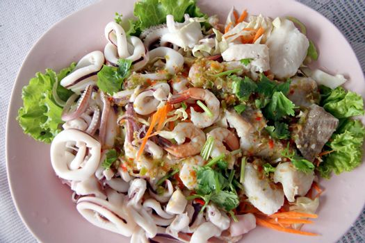 Mixed seafood salad in dish,The Thai food made form shrimp,fish,shellfish,squid and Assorted vegetables.