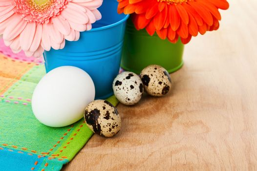 Easter setting with quail eggs and pink and orange gerberas