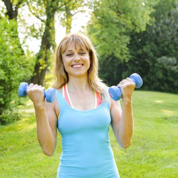 Portrait of female fitness instructor exercising with small weights in green park