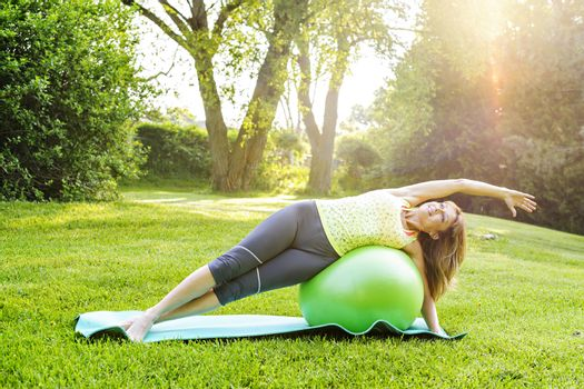 Female fitness instructor using yoga exercise ball  outdoors in morning sunshine