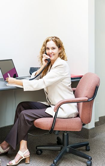 Businesswoman on phone talking and taking notes in office workstation
