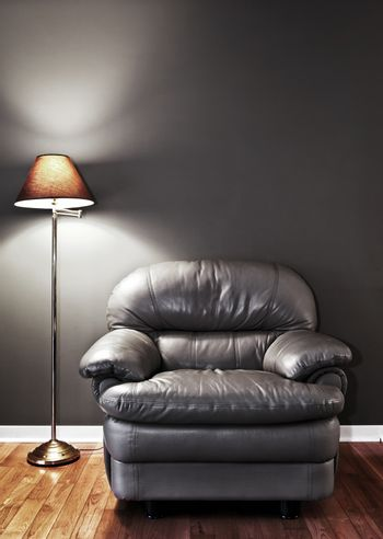 Leather chair and floor lamp against dark wall