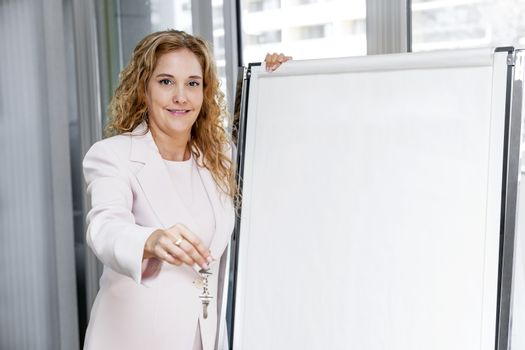 Smiling female real estate agent offering keys standing with blank flip chart