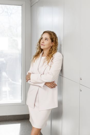 Thoughtful business woman standing in office hallway