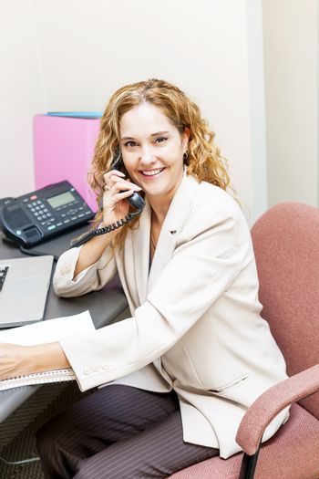 Smiling businesswoman on phone in office workstation