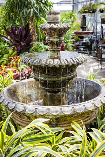 Cascading concrete fountain in garden nursery store with water flowing