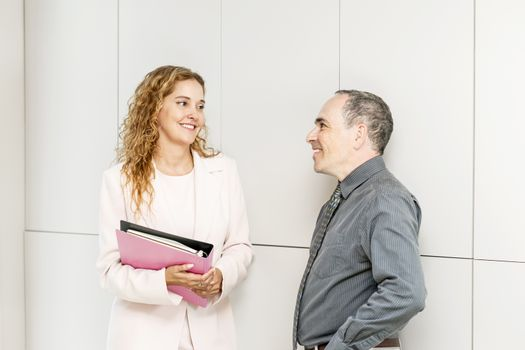 Man and woman discussing work in business office hallway