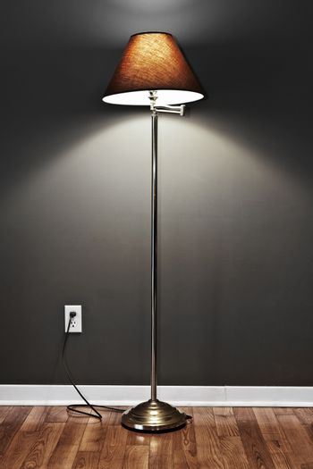 Tall floor lamp with metal base and dark lampshade on hardwood flooring in room