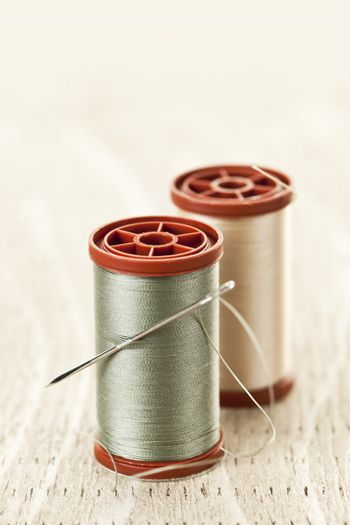Two spools of thread with needle for sewing