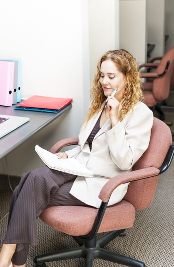 Businesswoman thinking of ideas in office workstation