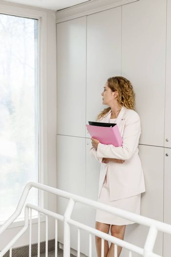 Serious thoughtful business woman standing in office hallway holding binder looking out window