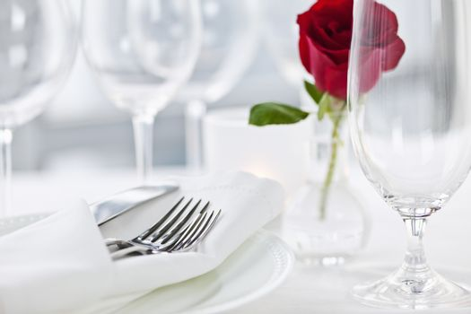 Romantic restaurant table setting with rose candle plates and cutlery