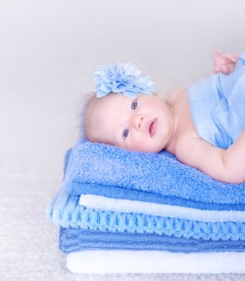 Sweet baby girl lying down on fresh soft blue towels with flower in head, stylish accessories for child, healthy lifestyle, happy childhood concept