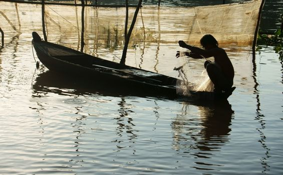 silhouette  's fisherman sitting on row boat, pick up the net, repair for fishing to catch fish on river at morning in flood season