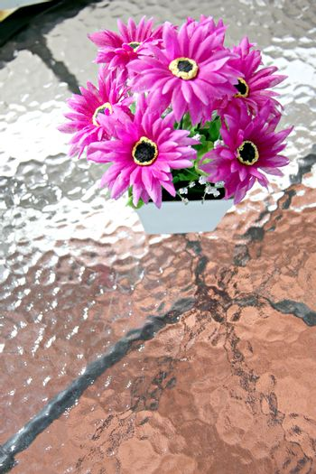 Purple flowers on the table glass and Patterned has mirror.
