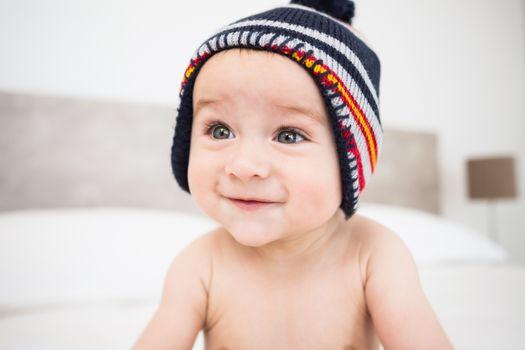 Baby boy wearing knit hat looking away