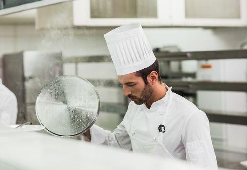 Handsome chef lifting a lid off a pot