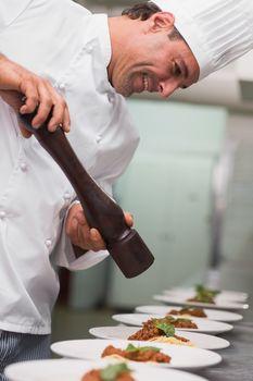 Happy chef grinding pepper over spaghetti dish