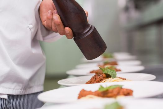 Chef grinding pepper over spaghetti dish