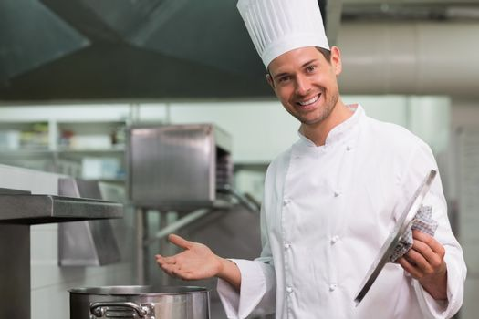 Chef holding a lid smiling at camera