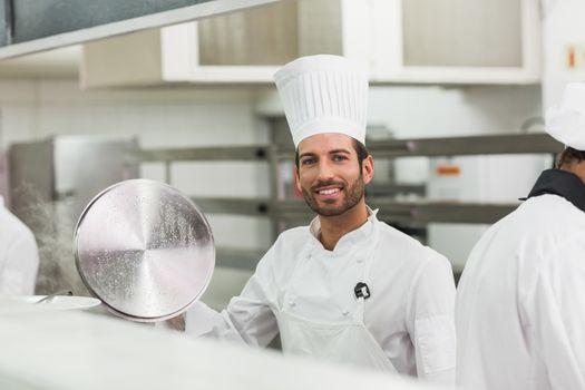 Happy chef lifting a lid off a pot