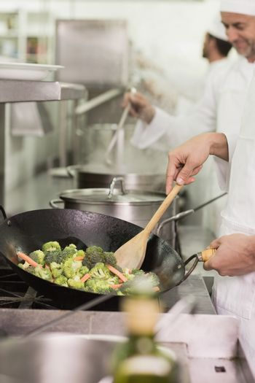 Chef frying broccoli in a wok