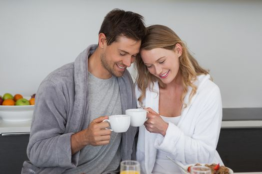 Happy young couple with coffee cups in the kitchen at home