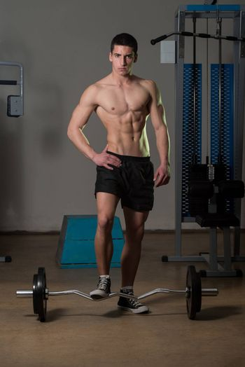 Young Muscular Men Standing By The Barbell