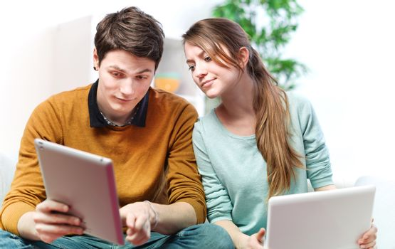 Beautiful young man showing something in his girlfriend on a touchpad