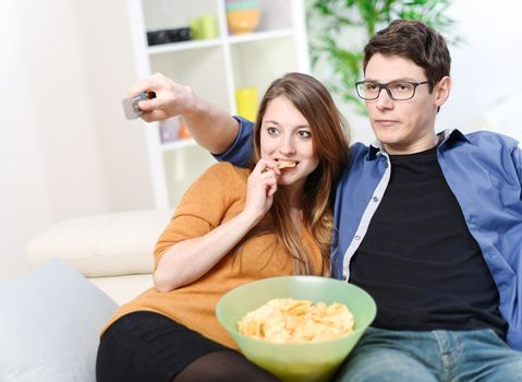 Very cute young couple eating and watching television on a couch