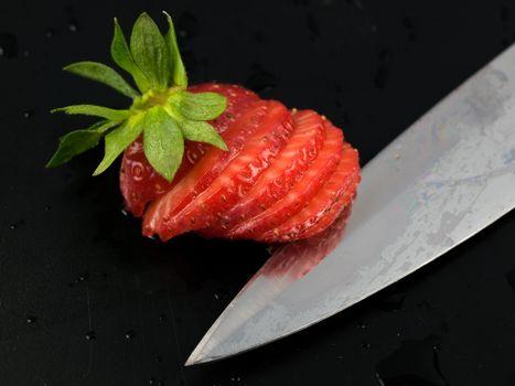 sliced srawberry with kife on black
