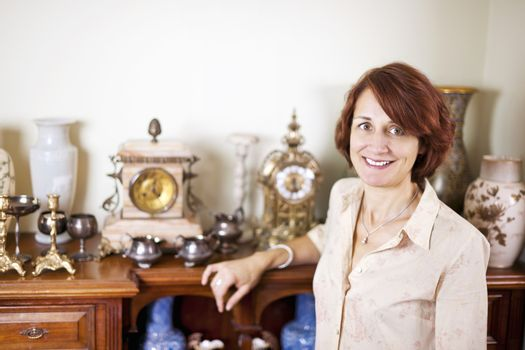 Happy proud woman standing next to her collection of antiques