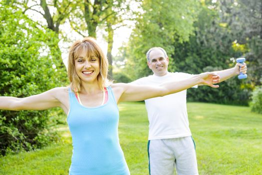 Female fitness instructor exercising with middle aged man outdoors in summer park