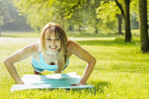 Female fitness instructor exercising doing pushups in green summer park