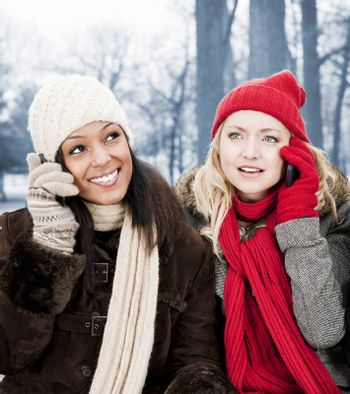 Portrait of two young female friends on the phone outdoors in winter