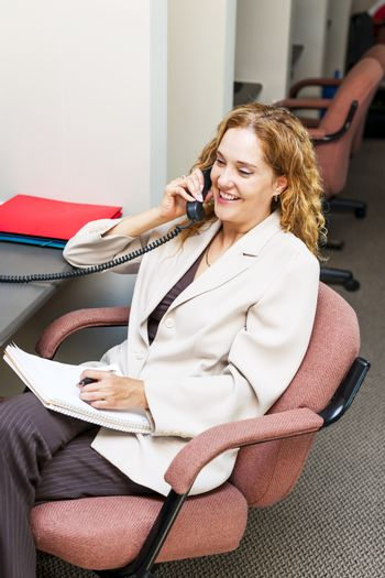 Happy businesswoman on phone taking notes in office workstation