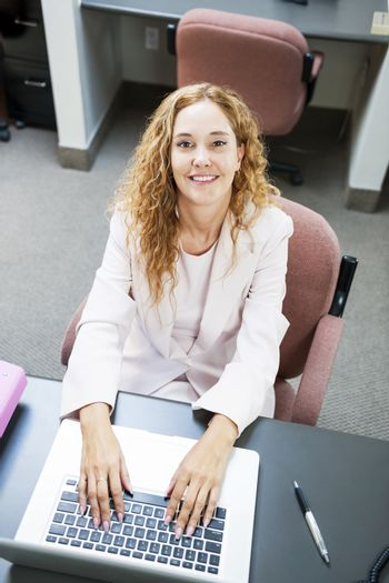Smiling businesswoman sitting at workstation in office with computer